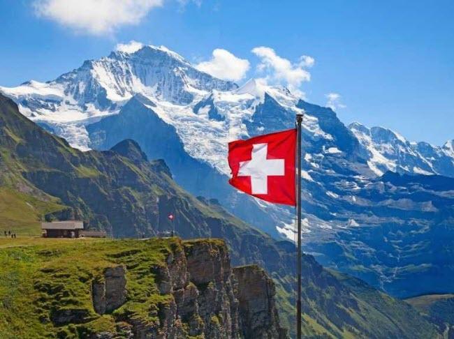 развевающийся на ветру флаг благословенной страны Швейцарии на фоне горных ландшафтов
