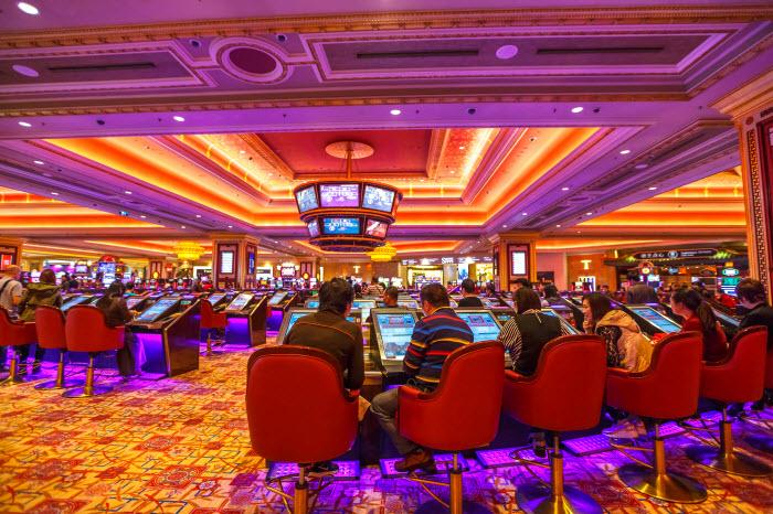 толпы китайцев спускают деньги за игровыми столами внутри казино Venetian в Макао